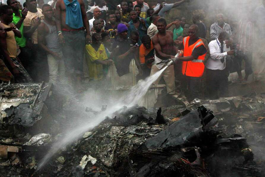 People gather at the site of a plane crash in Lagos, Nigeria, Sunday, June 3, 2012.  The passenger p