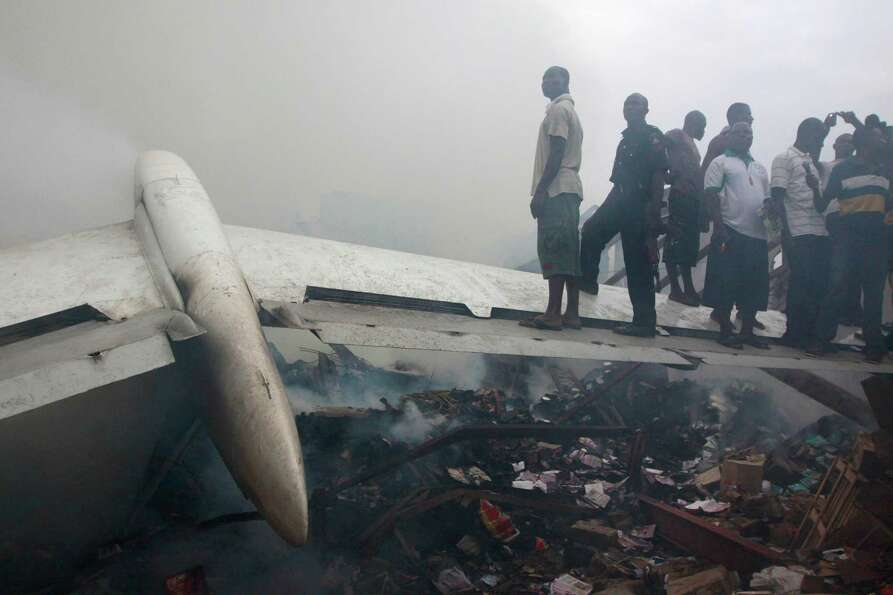 People stand on a wing of a wrecked passenger plane in Lagos, Nigeria, Sunday, June 3, 2012.  All 15