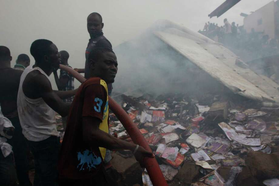 Rescue workers search for survivals at the site of a plane crash in Lagos, Nigeria, Sunday, June 3, 2012.  A passenger plane carrying more than 150 people crashed in Nigeria's largest city on Sunday, government officials said. Firefighters pulled at least one body from a building that was damaged by the crash and searched for survivors as several charred corpses could be seen in the rubble.(AP Photo/Sunday Alamba) Photo: Sunday Alamba, Associated Press / AP