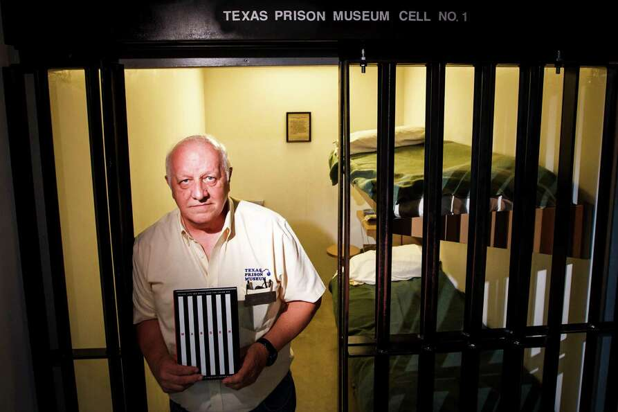 Former Texas Warden Jim Willett holds a book he wrote on the prison system while standing at the Tex