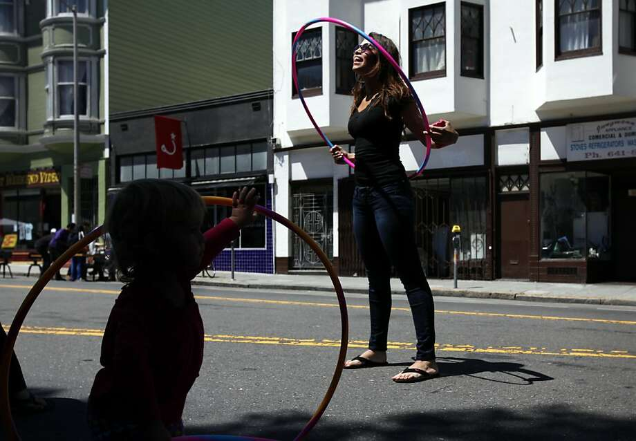 Carolina Builes, of San Francisco, right, takes advantage of hula hoops set out for people participating in Sunday Streets on Valencia St. in San Francisco, Calif. Sunday, June 3, 2012. Photo: Sarah Rice, Special To The Chronicle