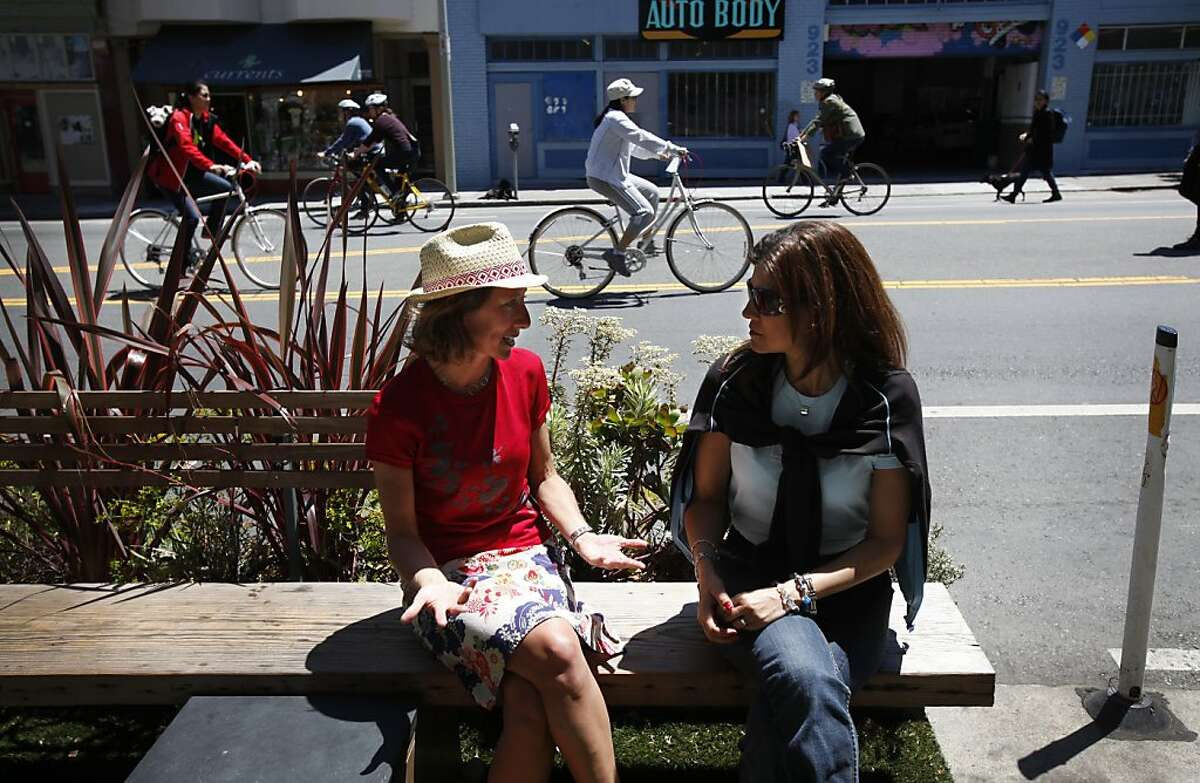 Leah Shahum, left, the executive director of the San Francisco Bicycle Coalition, talked with Claudia Penalosa, right, wife of Gil Penalosa, who created Sunday Streets, during the Sunday Streets closure on Valencia St. in San Francisco, Calif. Sunday, June 3, 2012.