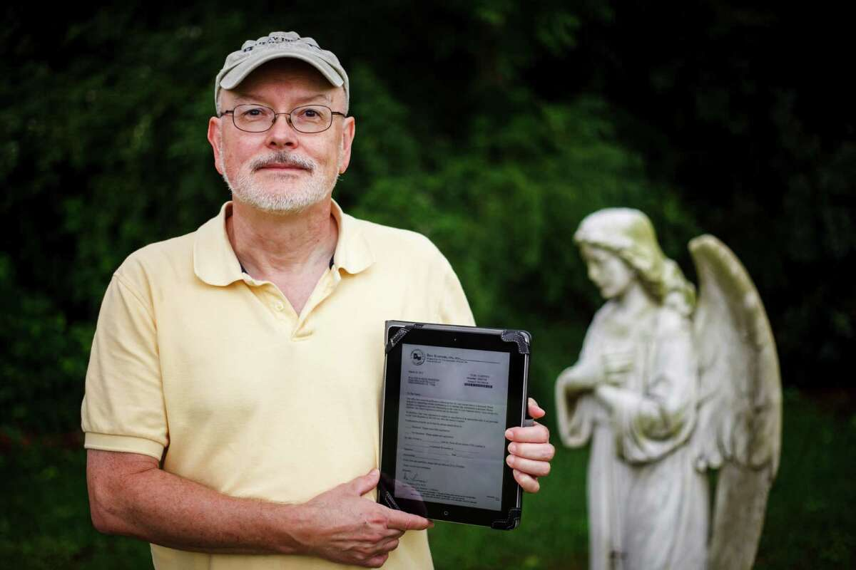 Walter Pinkston - shown at Friendswood Friends Church Cemetery early last month - holds a copy of a document sent to him asking if he was dead and saying that he needed to prove he was not or he would be purged from voter rolls.