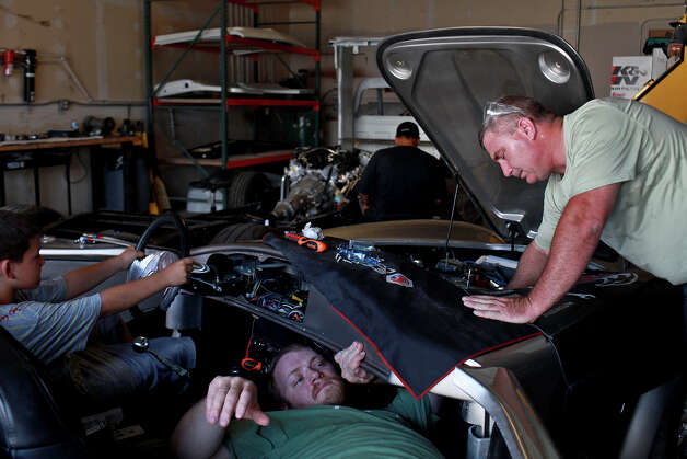 Sgt. Chris Leverkuhn, who was injured in Iraq, bottom, works with Sgt. First Class Vic Hash, right, who was injured in Afghanistan, while Robert Rodriguez, 9, pretends to drive, to get the Cobra he and other soldiers built with the Automotivation program running at Lay'N Color in Converse on May 25, 2012 in preparation for taking it to the Helotes Memorial Day Car Show. Rodriguez's father, Rob Rodriguez, lets Automotivation use space in his shop and has volunteered with the program for years. Photo: Lisa Krantz, San Antonio Express-News / San Antonio Express-News
