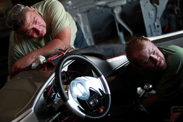 Chris Leverkuhn, who was injured in Iraq, right, works with Sgt. First Class Vic Hash, left, who was injured in Afghanistan, to get the Cobra running that they built with other soldiers with the Automotivation program at Lay'N Color in Converse on May 25, 2012 in preparation for taking it to the Helotes Memorial Day Car Show. Photo: Lisa Krantz, San Antonio Express-News / San Antonio Express-News