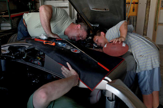 Chris Leverkuhn, who was injured in Iraq, bottom, works with Sgt. First Class Vic Hash, left, who was injured in Afghanistan, while Robert Rodriguez, 9, watches, to get the Cobra he and other soldiers built with the Automotivation program running at Lay'N Color in Converse on May 25, 2012 in preparation for taking it to the Helotes Memorial Day Car Show. Rodriguez's father, Rob Rodriguez, lets Automotivation use space in his shop and has volunteered with the program for years. Photo: Lisa Krantz, San Antonio Express-News / San Antonio Express-News
