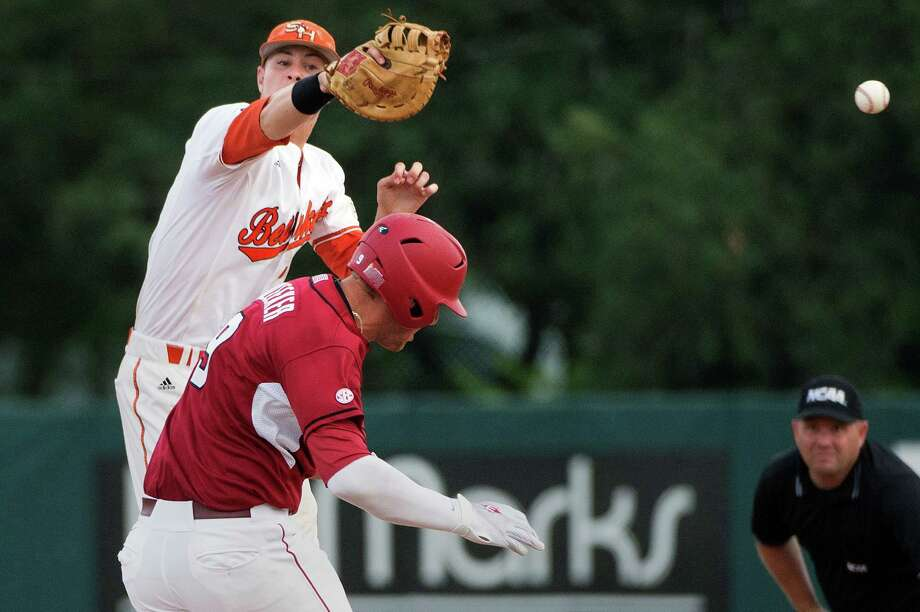 Arkansas' Derrick Bleeker is safe at first as the throw gets away from Sam Houston State first baseman Ryan O'Hearn, rear, during the fourth inning of an NCAA college baseball tournament regional game, Sunday, June 3, 2012, in Houston. (AP Photo/Houston Chronicle, Smiley N. Pool)  MANDATORY CREDIT Photo: Smiley N. Pool, Associated Press / © 2012  Houston Chronicle