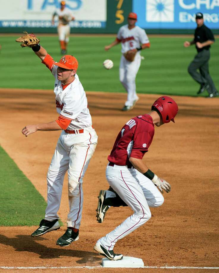 Arkansas' Brian Anderson, right, is safe at first as the throw gets away from Sam Houston State first baseman Ryan O'Hearn during the first inning of an NCAA college baseball tournament regional game, Sunday, June 3, 2012, in Houston. Anderson advance to second on the throwing error by shortstop Corey Toups and later scored in the inning. (AP Photo/Houston Chronicle, Smiley N. Pool) MANDATORY CREDIT Photo: Smiley N. Pool, Associated Press / © 2012  Houston Chronicle