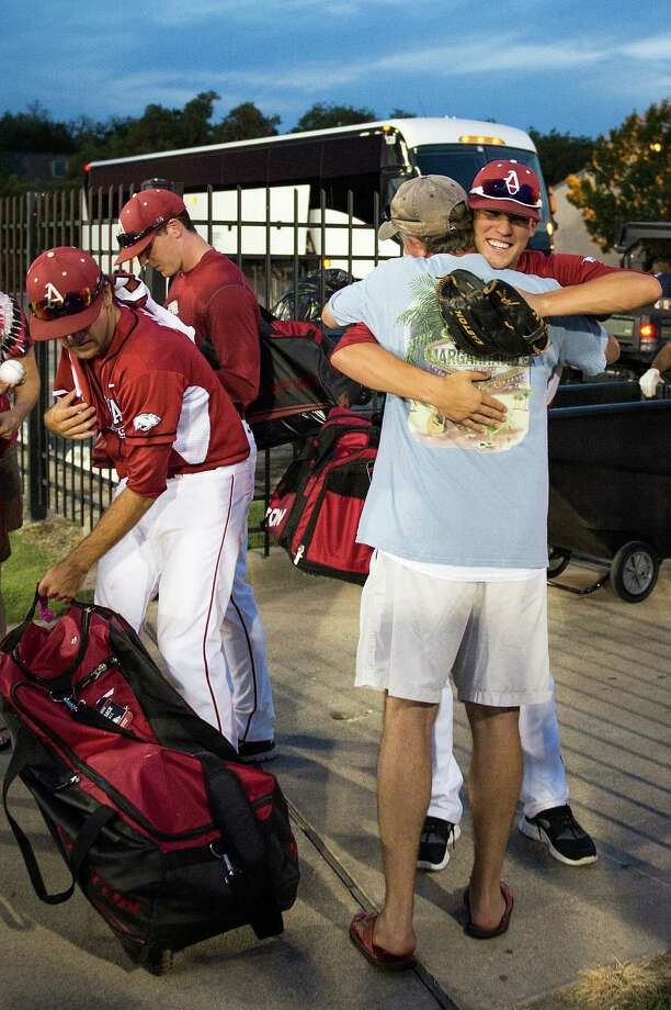 Arkansas pitcher Ty Wright gets a hug as the Razorbacks celebrate while they head to the bus after their victory over Sam Houston State after an NCAA college baseball tournament regional game Sunday, June 3, 2012, in Houston. Arkansas won the game 5-1 to win the regional. Photo: Smiley N. Pool, Houston Chronicle / © 2012  Houston Chronicle