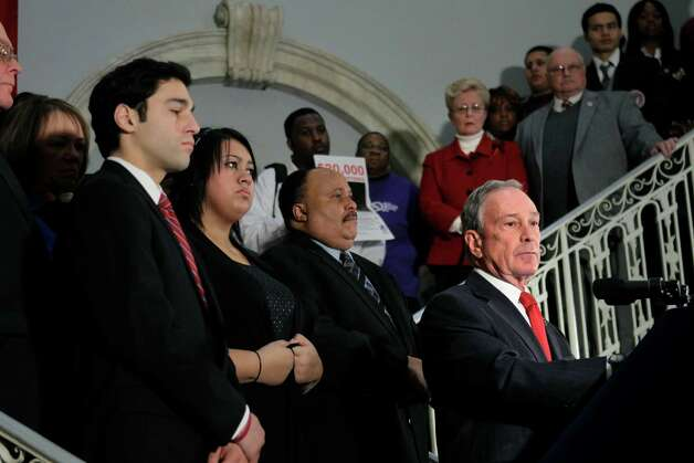 New York City Mayor Michael Bloomberg, right, joined by family and friends of those injured and killed in the shootings in Tucson, Ariz., at Virginia Tech and Columbine High School in Colorado, speaks about gun control during a news conference at City Hall in New York, Monday, Jan. 24, 2011.  (AP Photo/Seth Wenig) Photo: Seth Wenig / AP