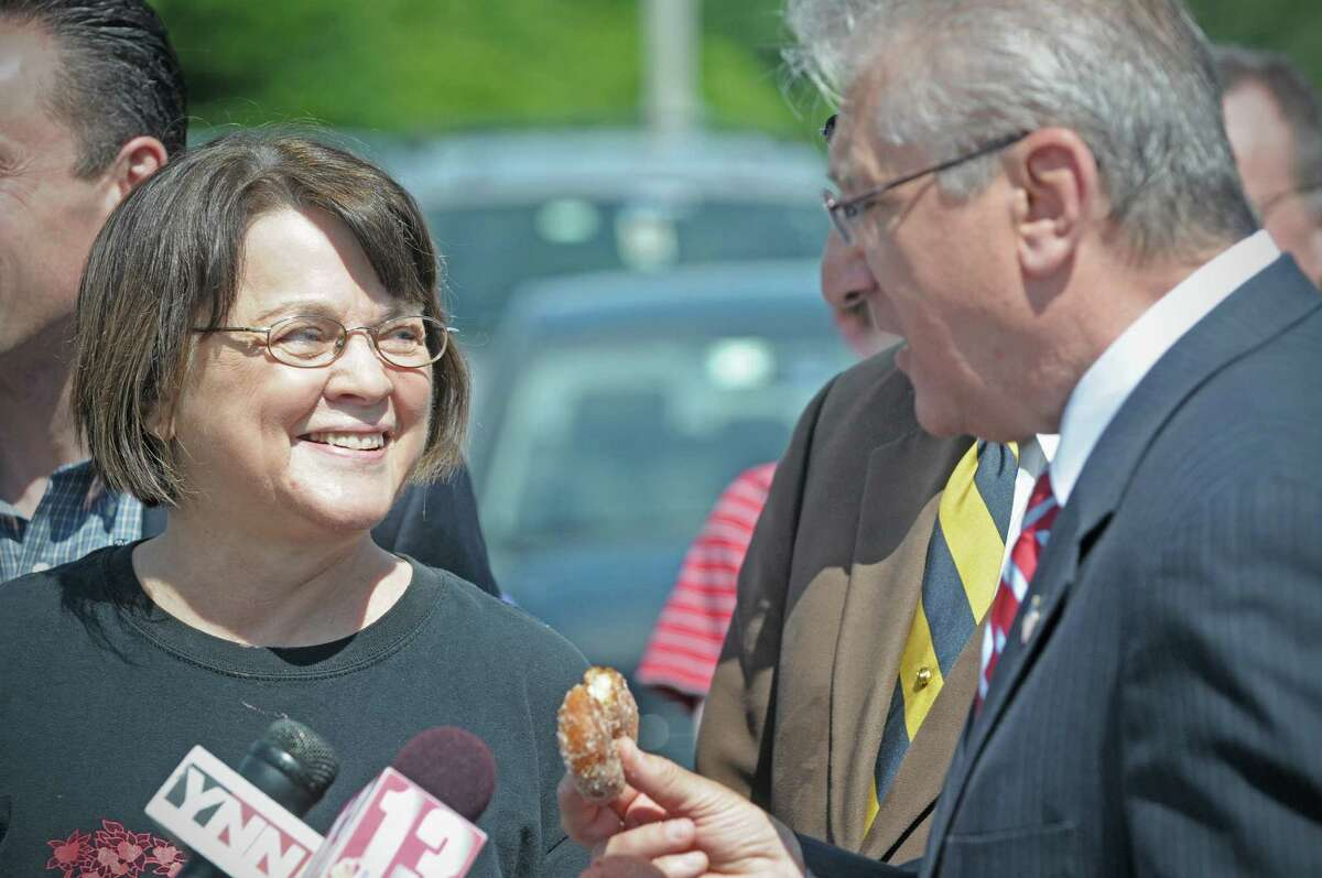 Isabel Prescott, left, owner of Riverview Orchards smiles as Assemblyman Jim Tedisco raves about the apple cider doughnuts from the orchard during a press event at Riverview Orchards on Sunday, June 3, 2012 in Rexford, NY. The event was held by legislators to announce new legislation, the ?Family Farmers and Apple Growers Relief Act? to help apple growers and farmers who have lost a significant amount of their crops due to the extreme weather. Isabel Prescott, owner of Riverview Orchards said that she's projecting that over 75% of their apple crop is lost due to weather. (Paul Buckowski / Times Union)