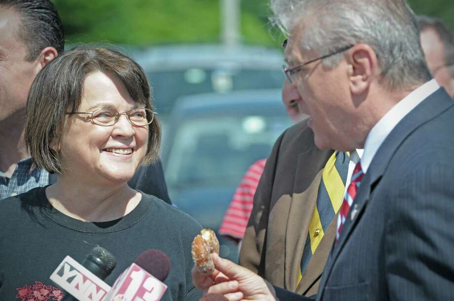 Isabel Prescott, left, owner of Riverview Orchards smiles as Assemblyman Jim Tedisco raves about the apple cider doughnuts from the orchard during a press event at Riverview Orchards on Sunday, June 3, 2012 in Rexford, NY.  The event was held by legislators to announce new legislation, the ?Family Farmers and Apple Growers Relief Act? to  help apple growers and farmers who have lost a significant amount of their crops due to the extreme weather.  Isabel Prescott, owner of Riverview Orchards said that she's projecting that over 75% of their apple crop is lost due to weather.  (Paul Buckowski / Times Union) Photo: Paul Buckowski / 00017930A