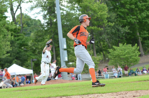 Shelton's Ryan Testani (30) rounds first base as Ridgefield's Patrick Molyneaux (21) waits for the throw during the Class LL baseball quarterfinals  at Shelton High School on Sunday, June 3, 2012. Photo: Amy Mortensen / Connecticut Post Freelance