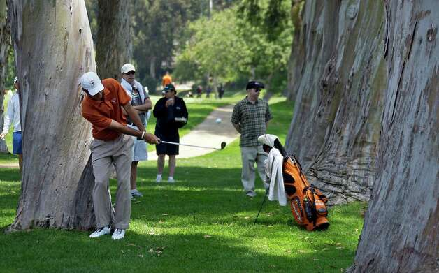 Dylan Frittelli, of the University of Texas, hits from behind trees on the 13th fairway on the way to victory over Alabama in the NCAA Division 1 men's golf championship at Riviera Country Club in Los Angeles, Sunday, June 3, 2012. Photo: Reed Saxon, Associated Press