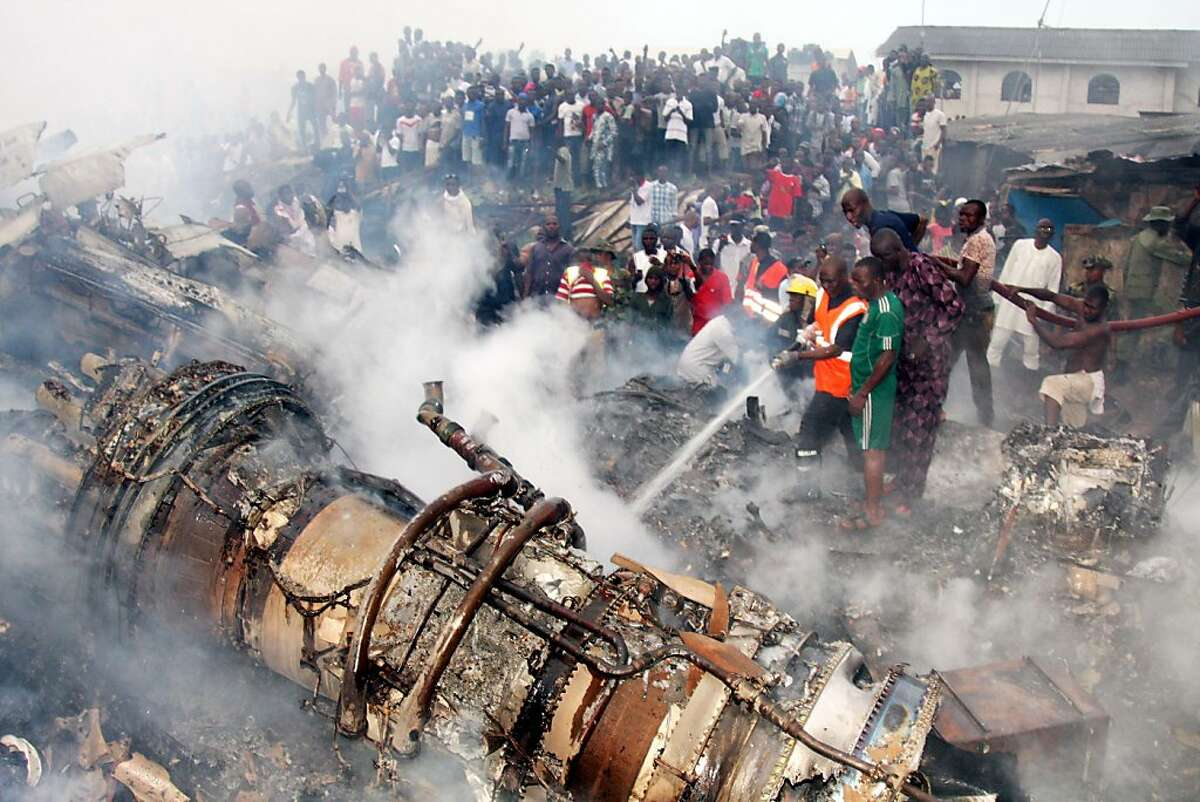 People gather at the site of a plane crash near the Lagos airport on June 3, 2012, in Lagos, Nigeria. A passenger plane carrying 153 people crashed into a two-story building in Nigeria's southwestern Lagos State on Sunday, killing all the people on board and 40 others on the ground. (Tunji Obasa/Xinhua/Zuma Press/MCT)