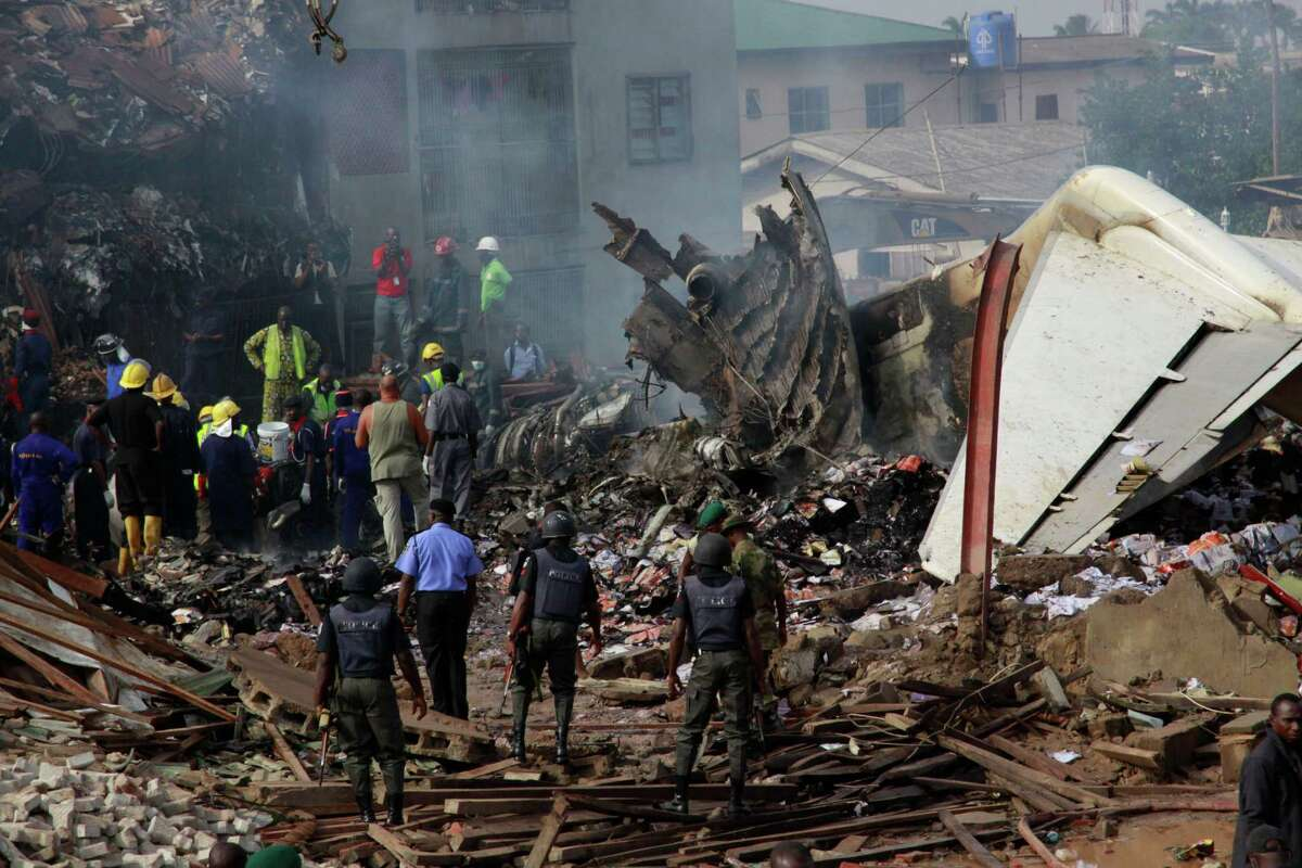 Policemen are seen at the site of a plane crash in Lagos, Nigeria, Monday,. A passenger plane carrying more than 150 people crashed in Nigeria's largest city on Sunday, government officials said. Firefighters pulled at least one body from a building that was damaged by the crash and searched for survivors as several charred corpses could be seen in the rubble.(AP Photo/Sunday Alamba)