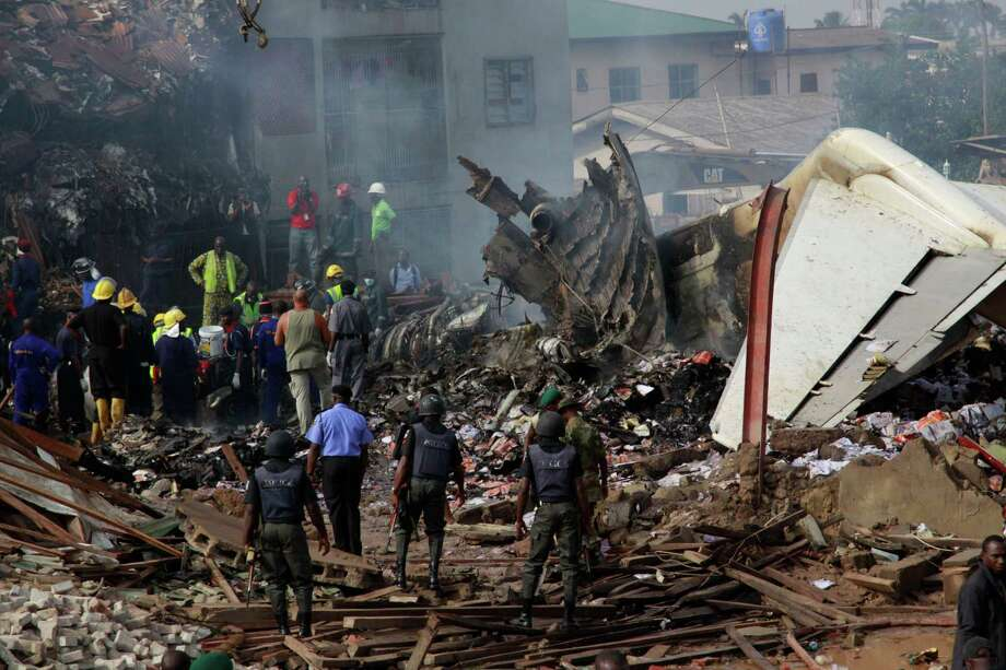 Policemen are seen at the site of a plane crash in Lagos, Nigeria, Monday,. A passenger plane carrying more than 150 people crashed in Nigeria's largest city on Sunday, government officials said. Firefighters pulled at least one body from a building that was damaged by the crash and searched for survivors as several charred corpses could be seen in the rubble.(AP Photo/Sunday Alamba) Photo: Sunday Alamba, Ap/getty / AP2012