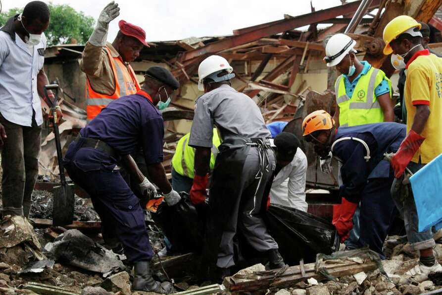 Rescue workers carry bodies at the site of a plane crash in Lagos, Nigeria, Monday, June 4, 2012. A