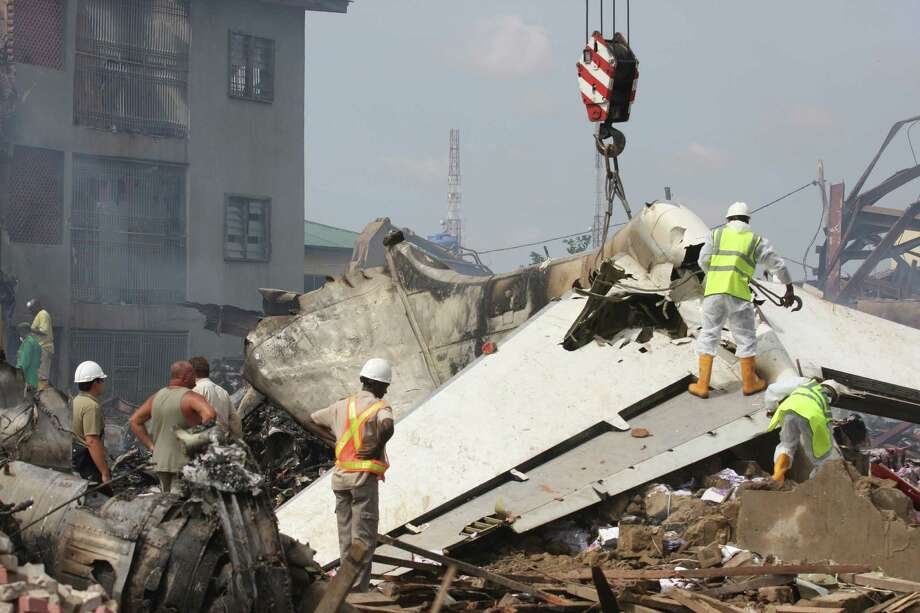 Investigators climb over the tail of a crashed commercial airplane in Lagos, Nigeria, Monday, June 4, 2012. Emergency workers in Nigeria used cadaver dogs and cranes to search for corpses Monday at the site where an American-built airliner plunged to earth, killing all 153 aboard. Rescue officials said they fear many more people may have perished on the ground in the crash Sunday. (AP Photo/Jon Gambrell) Photo: Jon Gambrell, Associated Press / AP