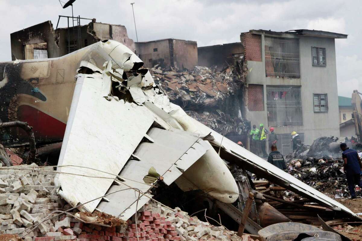The remains of a plane at the crash site in Lagos, Nigeria, Monday. A passenger plane carrying more than 150 people crashed in Nigeria's largest city on Sunday, government officials said. Firefighters pulled at least one body from a building that was damaged by the crash and searched for survivors as several charred corpses could be seen in the rubble.