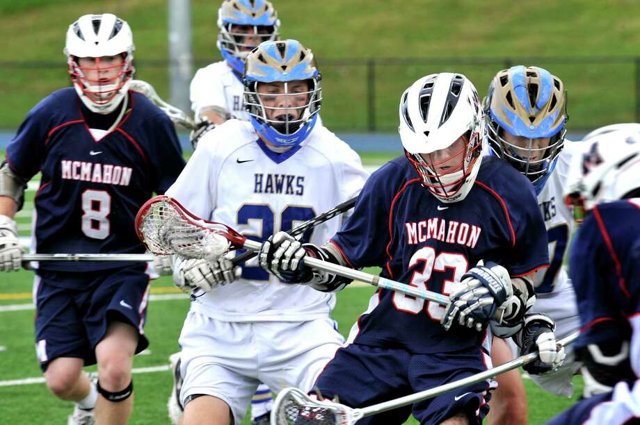 McMahon's Andrew D'Antonio, right center, carries the ball in the second round of the class L boys lacrosse state tournament in Newtown Saturday, June 2, 2012. Photo: Michael Duffy / The News-Times