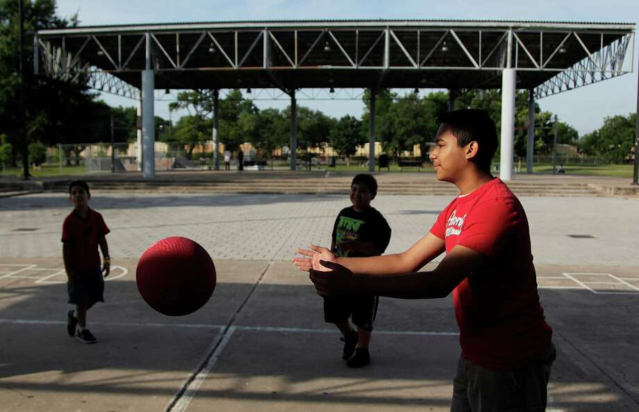 Christopher Guzman,13, plays with other children who are enrolled in the Summer Enrichment Program at Eastwood Park on Monday, June 4, 2012, in Houston.  The citywide program starts Monday, and is still accepting children for the summer program. The center has 56 children, but is prepared to handle 100 children. Children do activities at the center, go on field trips, use city pools, and are given a free lunch. Photo: Mayra Beltran, Houston Chronicle / Houston Chronicle