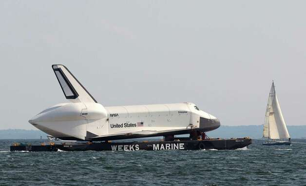 A sailboat passes the atmospheric test space shuttle Enterprise as it is towed past Coney Island in New York, Sunday, June 3, 2012.  The prototype space shuttle that arrived in New York City by air earlier this spring is on the move again, this time by sea, to its final resting place at the Intrepid Sea, Air and Space Museum on the west side of Manhattan. Photo: AP