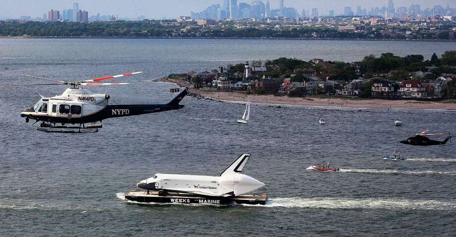 Helicopters fly above atmospheric test space shuttle Enterprise as its carried by barge past Coney Island on June 03, 2012 in New York City.  Enterprise is on its way to the Intrepid Sea, Air and Space Museum, where it will put on permanent display. Photo: Michael Nagle, Getty Images / 2012 Getty Images