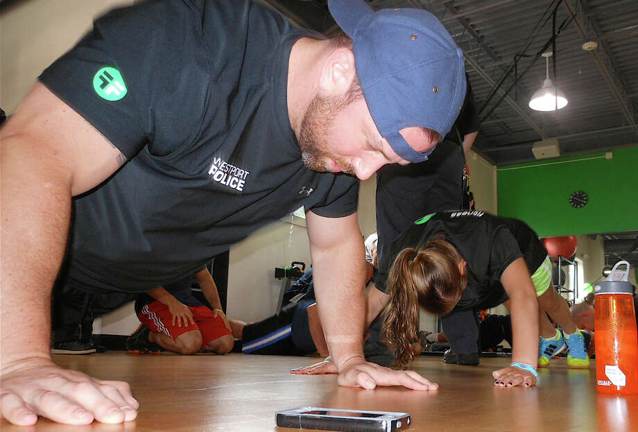 Fitness Factory co-owner Andy Berman and teammate Emily Bass knock out push-ups at the gym Saturday in a Push-Up-Athon to raise money to send sick children to the Hole in the Wall Gang Camp this summer. Photo: Mike Lauterborn / Westport News contributed