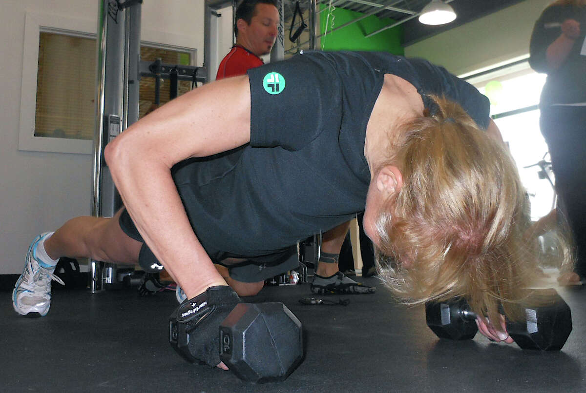 Fitness Factory co-owner Mary Sue Teplitz does push-ups at the gym Saturday in the Push-Up-Athon benefit.