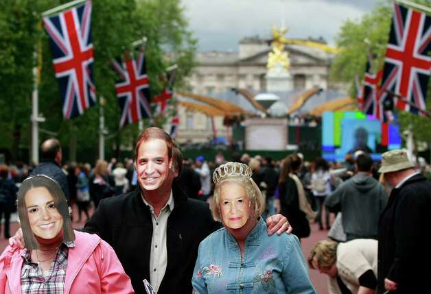 Members of the public wearing royal family face masks entertain themselves while waiting for the start of a pop music concert at Buckingham Palace, seen in centre background, to help celebrate Britain's Queen Elizabeth II's 60-year reign during Diamond Jubilee celebrations in London, Monday, June 4, 2012. Photo: Tim Hales, Ap / AP2012