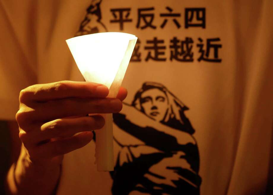 "A man wears a T-shirt with Chinese reading ""Vindicate June 4"" at a candlelight vigil at Hong Kong's Victoria Park in Hong Kong Monday to mark the 23rd anniversary of the June 4th Chinese military crackdown on the pro-democracy movement in Beijing. Photo: Ap"