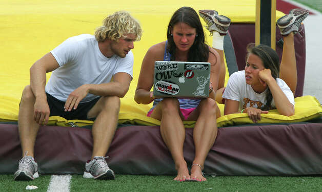 Texas State University pole vaulter Logan Cunningham (left) looks at wind conditions on the computer with his coach Brookelyn (cq) Dickson (center) and his girlfriend Leslie Ables (right) Thursday May 31, 2012. Cunningham is a former standout from Smithson Valley High School and will be competing next week in Des Moines, Iowa at the NCAA Outdoor Track and Field Championships. Photo: San Antonio Express-News