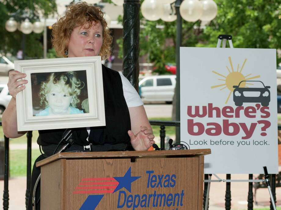 Cindy Quinn displays a photo of her daughter, who died of heatstroke, during a press conference to raise awareness and help prevent child tragedies from heatstroke, Monday, June 4, 2012, at Milam Park in San Antonio. Photo: Darren Abate, Darren Abate/Express-News