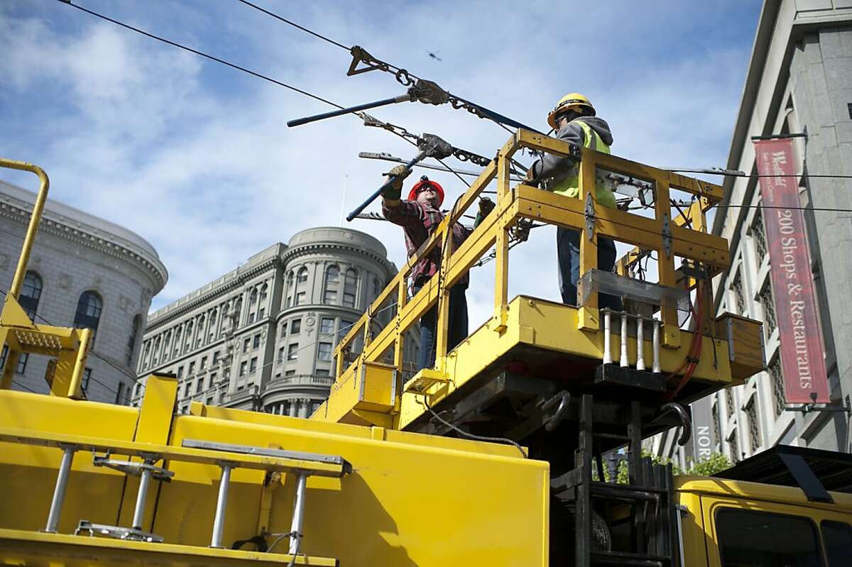 Workers repair cables that fell down after an incident involving a MUNI bus that injured three pedestrians at Market Street and 5th Street on Monday, June 4, 2012 in San Francisco, Calif.