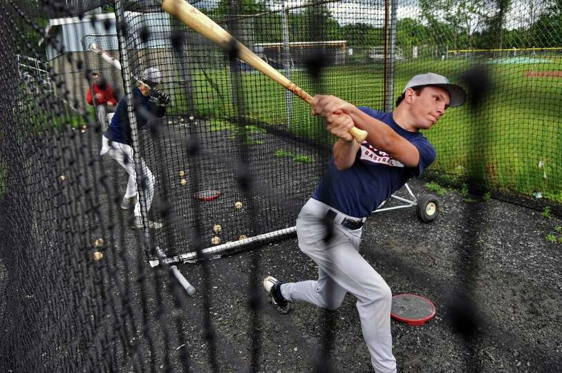 Columbia High School baseball player John Stanley takes swings in the batting cage as he and teammat