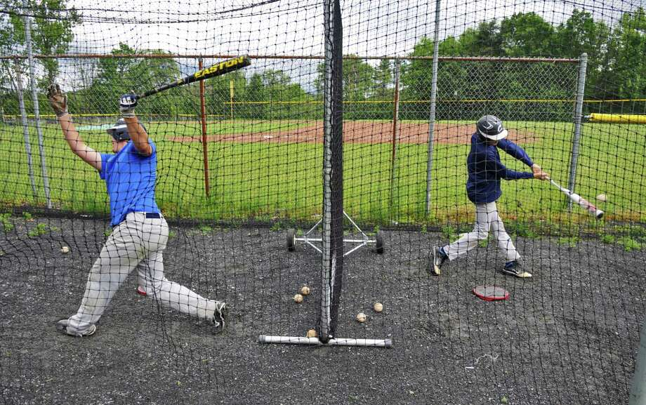 Columbia High School baseball player Tim Gaule, left, takes swings in the batting cage as he and his teammates prepare for their state tournament game, on Monday June 4, 2012 in East Greenbush, NY.  (Philip Kamrass / Times Union ) Photo: Philip Kamrass / 00017937A