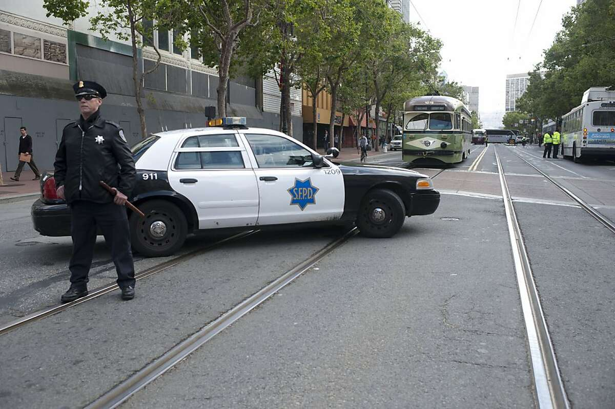 Tom Cunnane, a patrol officer, controls traffic on Market Street due to cables that fell on Market Street and 5th Street on Monday, June 4, 2012 in San Francisco, Calif.