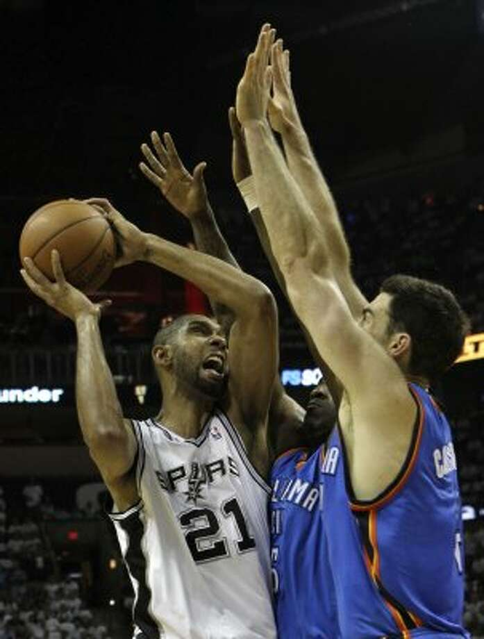 San Antonio Spurs' Tim Duncan (21) goes to the basket against Oklahoma City Thunder's Kendrick Perkins (5) and Oklahoma City Thunder's Nick Collison (4) during the first half of game five of the NBA Western Conference Finals in San Antonio, Texas on Monday, June 4, 2012. (Kin Man Hui / San Antonio Express-News)