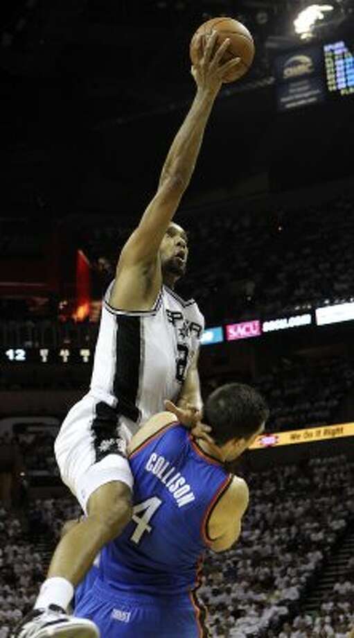 San Antonio Spurs' Tim Duncan (21) goes to the basket over Oklahoma City Thunder's Nick Collison (4), drawing a charge call, during the first half of game five of the NBA Western Conference Finals in San Antonio, Texas on Monday, June 4, 2012. (Kin Man Hui / San Antonio Express-News)