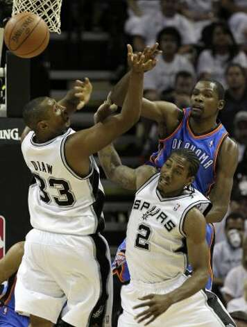 Oklahoma City Thunder's Kevin Durant (35) passes the ball over San Antonio Spurs' Boris Diaw (33) and San Antonio Spurs' Kawhi Leonard (2)  during the first half of game five of the NBA Western Conference Finals in San Antonio, Texas on Monday, June 4, 2012. (Kin Man Hui / San Antonio Express-News)