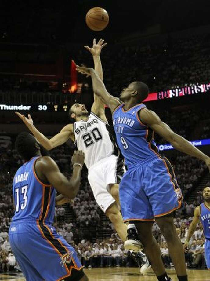 San Antonio Spurs' Manu Ginobili (20) shoots over Oklahoma City Thunder's Serge Ibaka (9) and Oklahoma City Thunder's James Harden (13) during the first half of game five of the NBA Western Conference Finals in San Antonio, Texas on Monday, June 4, 2012. (Kin Man Hui / San Antonio Express-News)