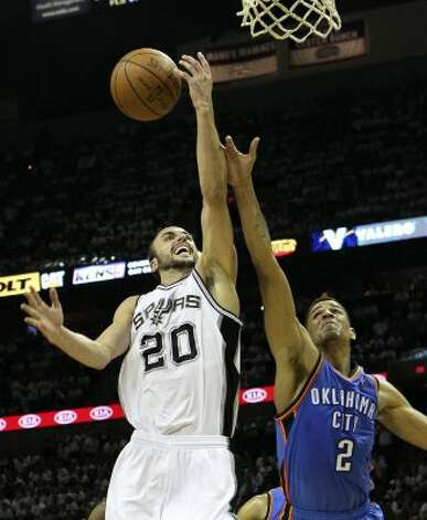 San Antonio Spurs' Manu Ginobili (20) goes to the basket against Oklahoma City Thunder's Thabo Sefolosha (2) during the first half of game five of the NBA Western Conference Finals in San Antonio, Texas on Monday, June 4, 2012. (Kin Man Hui / San Antonio Express-News)