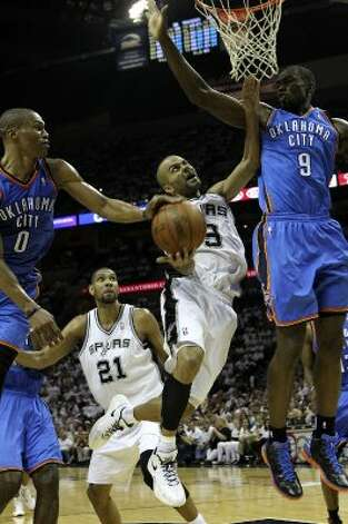 Oklahoma City Thunder's Russell Westbrook (0) strips the ball from San Antonio Spurs' Tony Parker (9) near Oklahoma City Thunder's Serge Ibaka (9) during the first half of game five of the NBA Western Conference Finals in San Antonio, Texas on Monday, June 4, 2012. (Kin Man Hui / San Antonio Express-News)