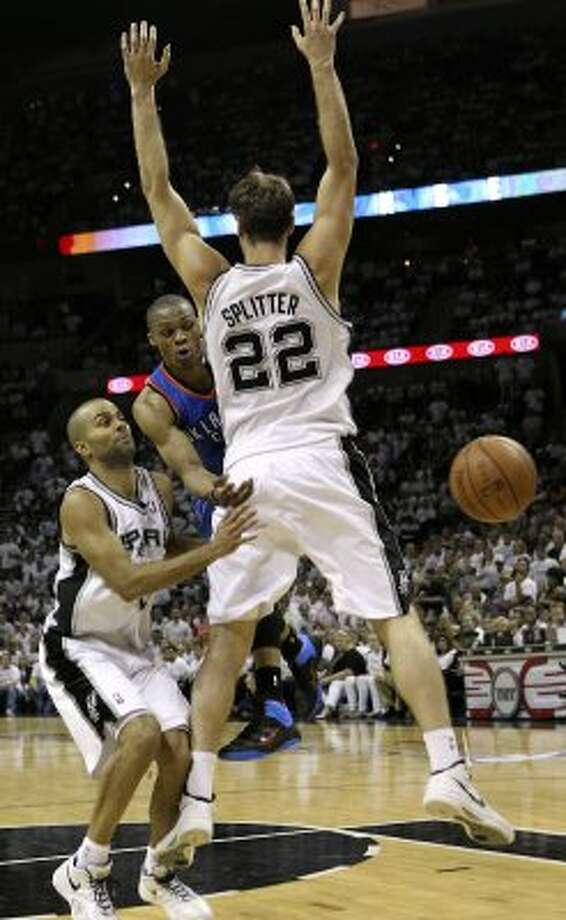 Oklahoma City Thunder's Russell Westbrook (0) passes around San Antonio Spurs' Tiago Splitter (22) and San Antonio Spurs' Tony Parker (9) during the second half of game five of the NBA Western Conference Finals in San Antonio, Texas on Monday, June 4, 2012. (San Antonio Express-News)