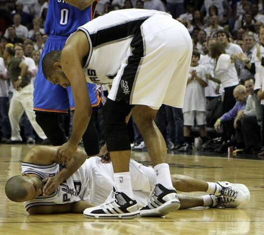 San Antonio Spurs' Tim Duncan (21) helps up San Antonio Spurs' Tony Parker (9) during the second half of game five of the NBA Western Conference Finals in San Antonio, Texas on Monday, June 4, 2012.  The Thunder won 108-103. (Kin Man Hui / San Antonio Express-News)