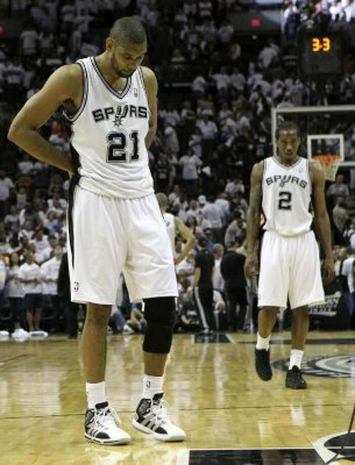 San Antonio Spurs' Tim Duncan (21) and San Antonio Spurs' Kawhi Leonard (2) walk on the court near the end of game five of the NBA Western Conference Finals in San Antonio, Texas on Monday, June 4, 2012.  The Thunder won 108-103. (Kin Man Hui / San Antonio Express-News)