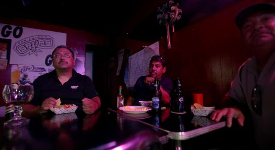 (From left) Joe Robles, Armando Robles and Pablo Pereda eat their free tacos while watching the Spurs game against the Oklahoma City Thunder, Monday, June 4, 2012, at Tony's. The group has been coming to the bar for about five years and show up at least twice a week. (SAN ANTONIO EXPRESS-NEWS)