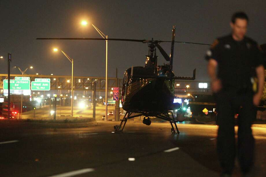 A San Antonio police officer walks behind one of the department's Blue Eagle helicopters, which made an emergency landing near Lee Hall Street and Interstate 10 on Monday night after a warning light indicated the engine could malfunction. Photo: Kevin Martin, San Antonio Express-News / © 2012 San Antonio Express-News