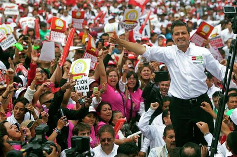 Mexican presidential candidate Enrique Pena Nieto of the Revolutionary Institutional Party (PRI) wav